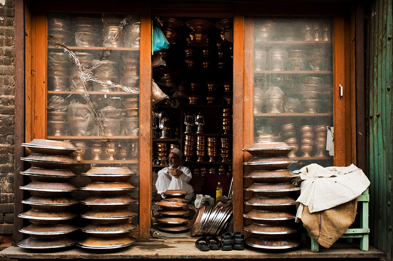 A salesman of silver and copper goods sits idle on a slow business day.  - Srinagar, Kashmir, India - Daily Travel Photos