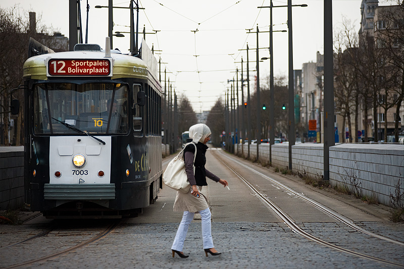 A tram waits for a Muslim woman to cross Amerikalei. - Antwerp, Belgium - Daily Travel Photos