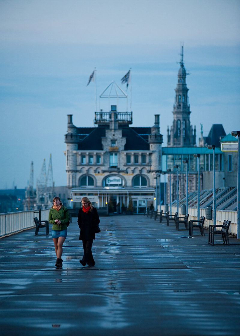 Two women take an evening stroll on the path connecting Het Steen and a bistro/tavern with port cranes dotting the skyline. - Antwerp, Belgium - Daily Travel Photos