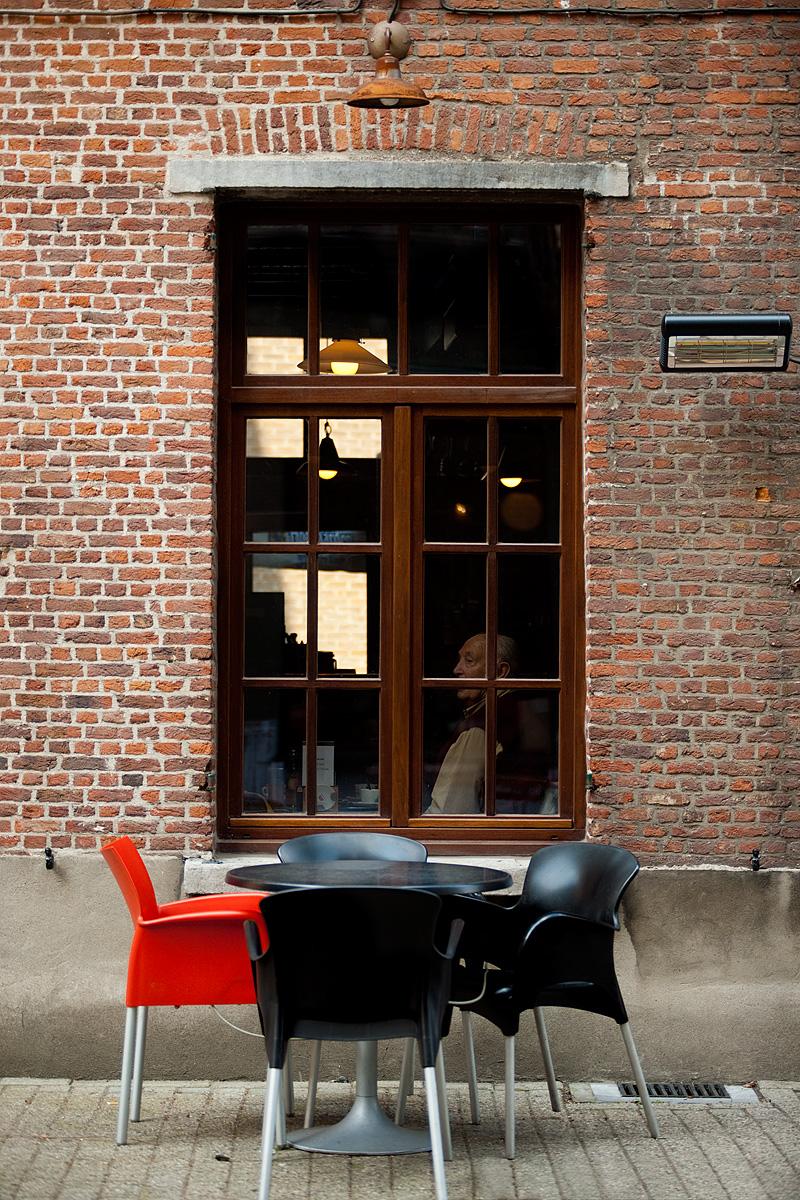 An older gentleman enjoys tea inside the window of a cafe. - Antwerp, Belgium - Daily Travel Photos