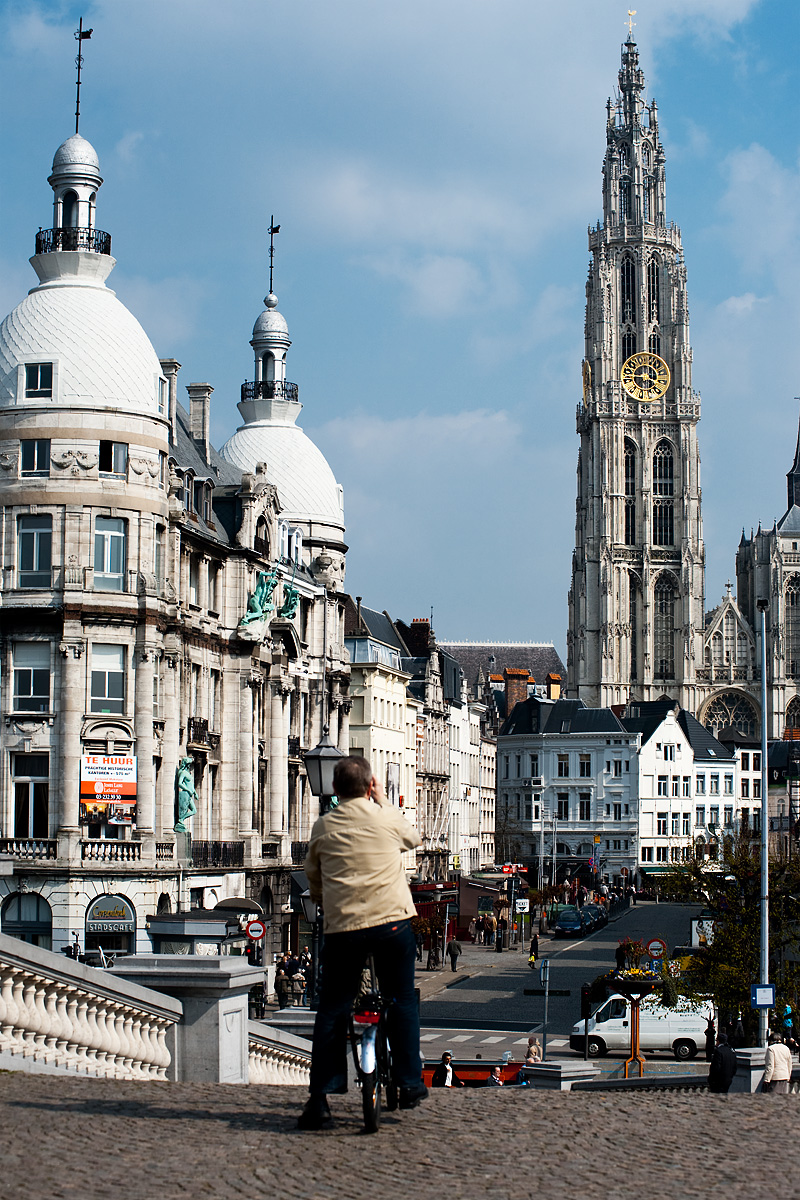A local on a bicycle snaps a quick photo of the Cathedral of Our Lady from the Scheldt River belvedere. - Antwerp, Belgium - Daily Travel Photos