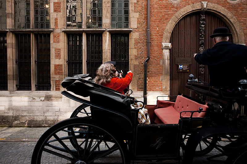 The driver of a horse and buggy gestures toward the door plaque of the Plantin-Moretus museum. - Antwerp, Belgium - Daily Travel Photos