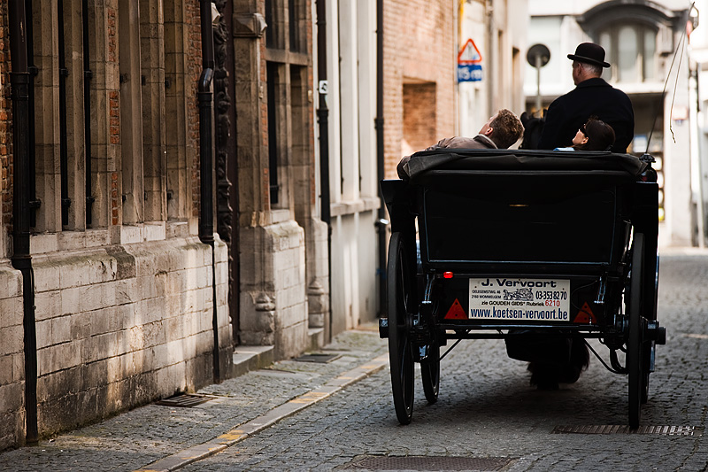 A tourist couple look up as they ride a horse and buggy down an alleyway adjacent to the Plantin-Moretus museum. - Antwerp, Belgium - Daily Travel Photos