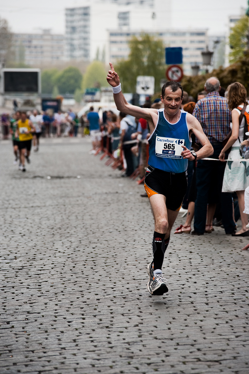 A marathon runner gestures as he nears the finish line. - Antwerp, Belgium - Daily Travel Photos