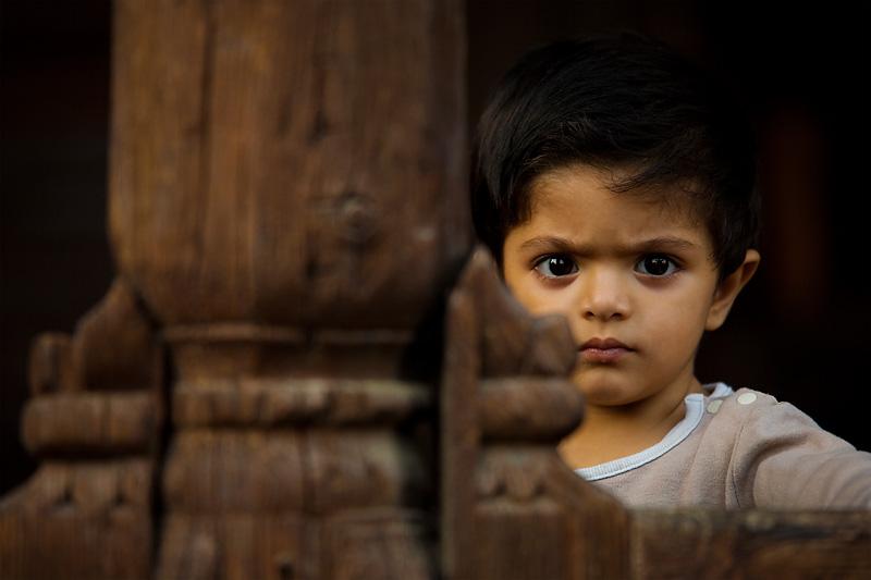 A young boy hides partially behind a wooden column. - Srinagar, Kashmir, India - Daily Travel Photos