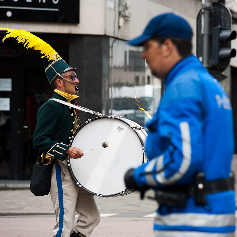 A drummer leads crosses paths with a policeman. - Antwerp, Belgium - Daily Travel Photos