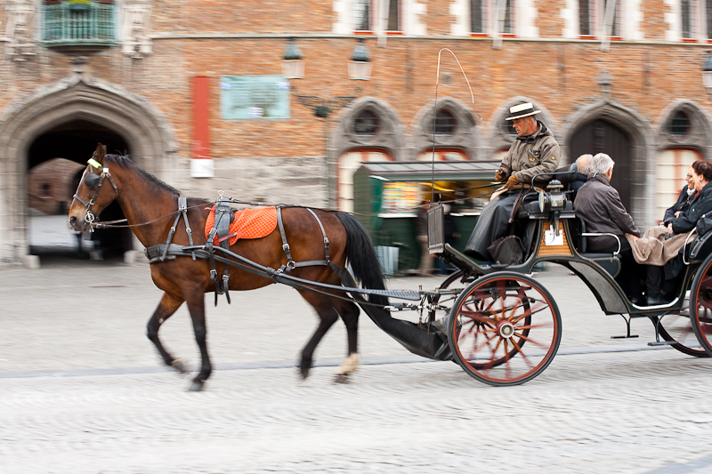 A tourist horse and buggy glide past the belfry on Grote Markt. - Brugge, Belgium - Daily Travel Photos