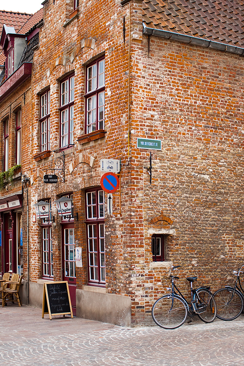 Bicycles parked outside a traditional brick building. - Brugge, Belgium - Daily Travel Photos