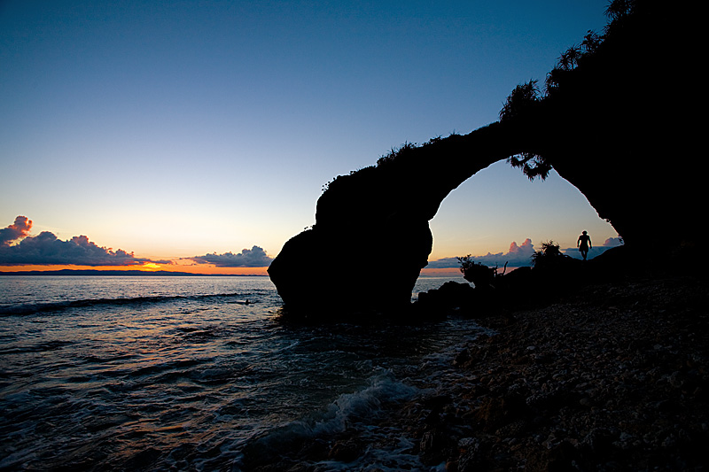 A Czech backpacker walks through a naturally formed arch at sunset. - Neil Island, Andaman, India - Daily Travel Photos