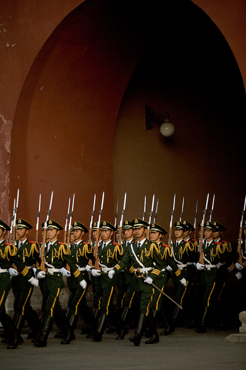 Soldiers walk through a gateway after completing the flag-lowering ceremony on Tienanmen Square. - Beijing, China - Daily Travel Photos