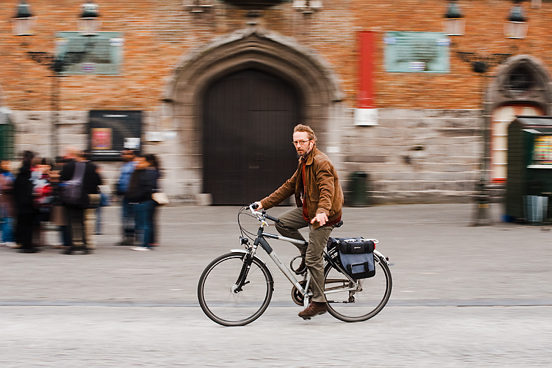 A bicyclist is shown against a motion-blurred background. - Brugge, Belgium - Daily Travel Photos