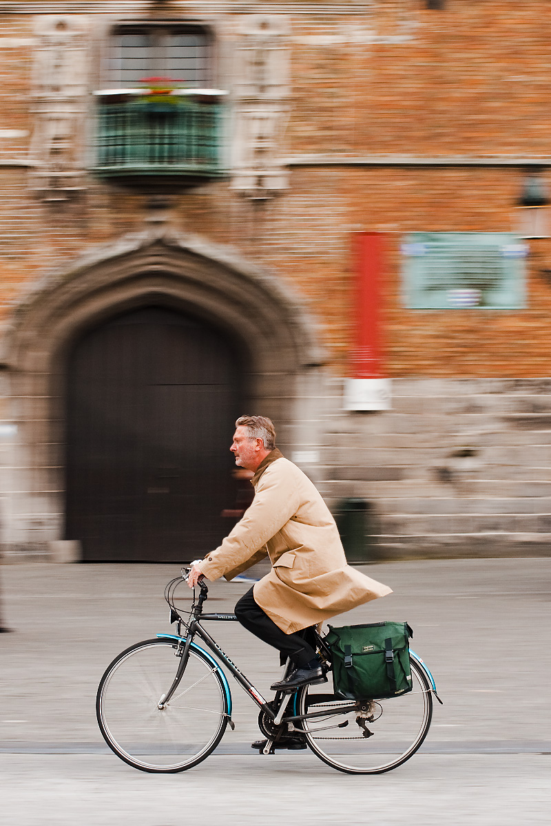 Panning capture of a bicyclist in front of Grote Markt's belfry. - Brugge, Belgium - Daily Travel Photos