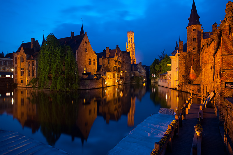 A canal reflects the facades of beautiful traditional buildings. - Brugge, Belgium - Daily Travel Photos