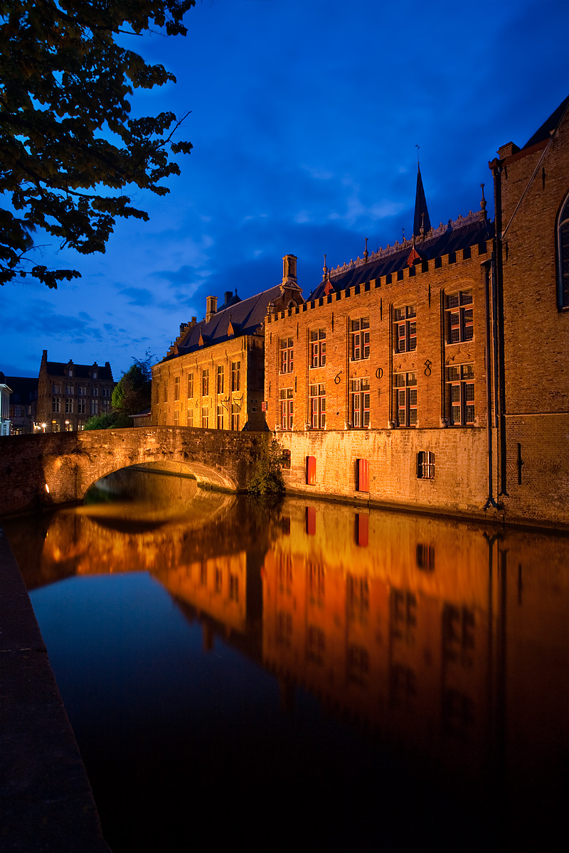 A canal reflects a bridge and traditional old buildings in historic Bruges. - Brugge, Belgium - Daily Travel Photos