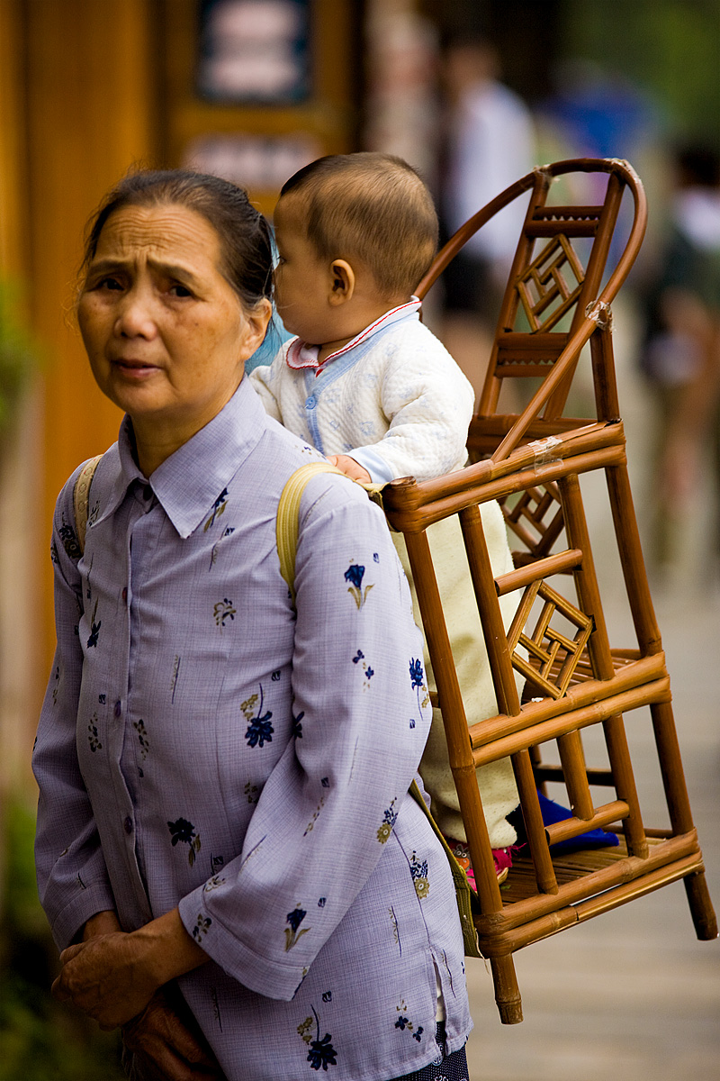 A grandmother carries a baby in a traditional wooden baby carrier. - Fenghuang, Hunan, China - Daily Travel Photos