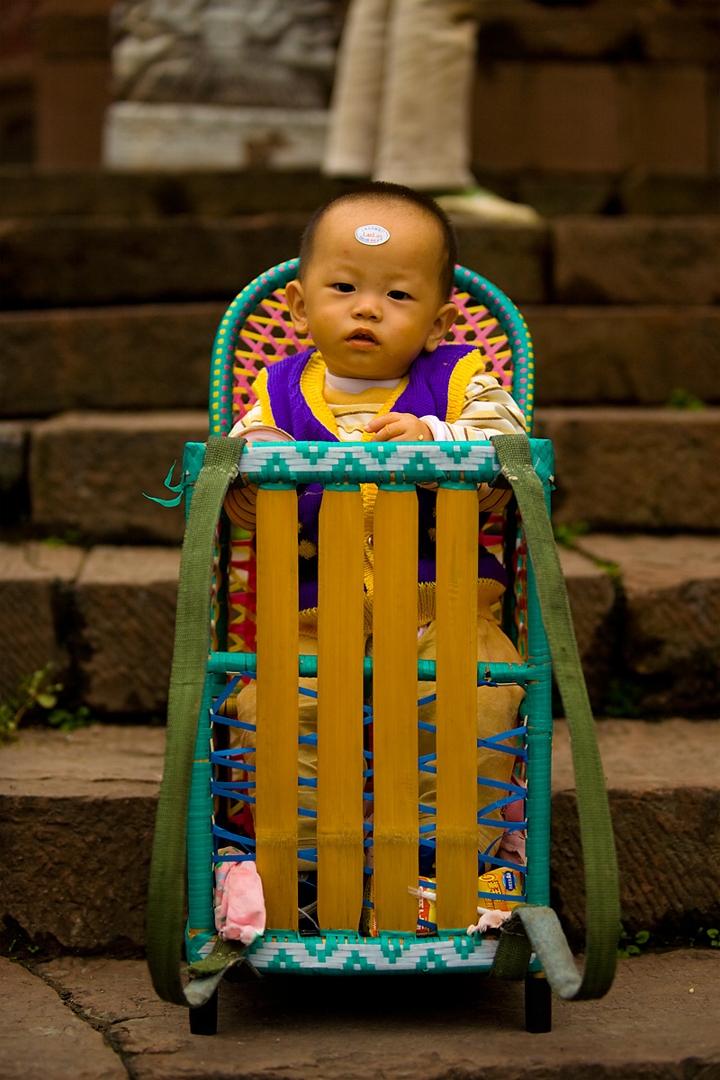 A Chinese baby is left to enjoy his baby chair cum carrier. - Fenghuang, Hunan, China - Daily Travel Photos