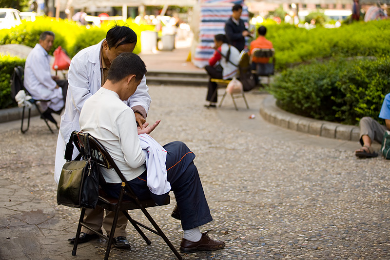 A street earwax removal technician diagnoses the extracted contents of a patient's ear.  - Guiyang, Guizhou, China - Daily Travel Photos