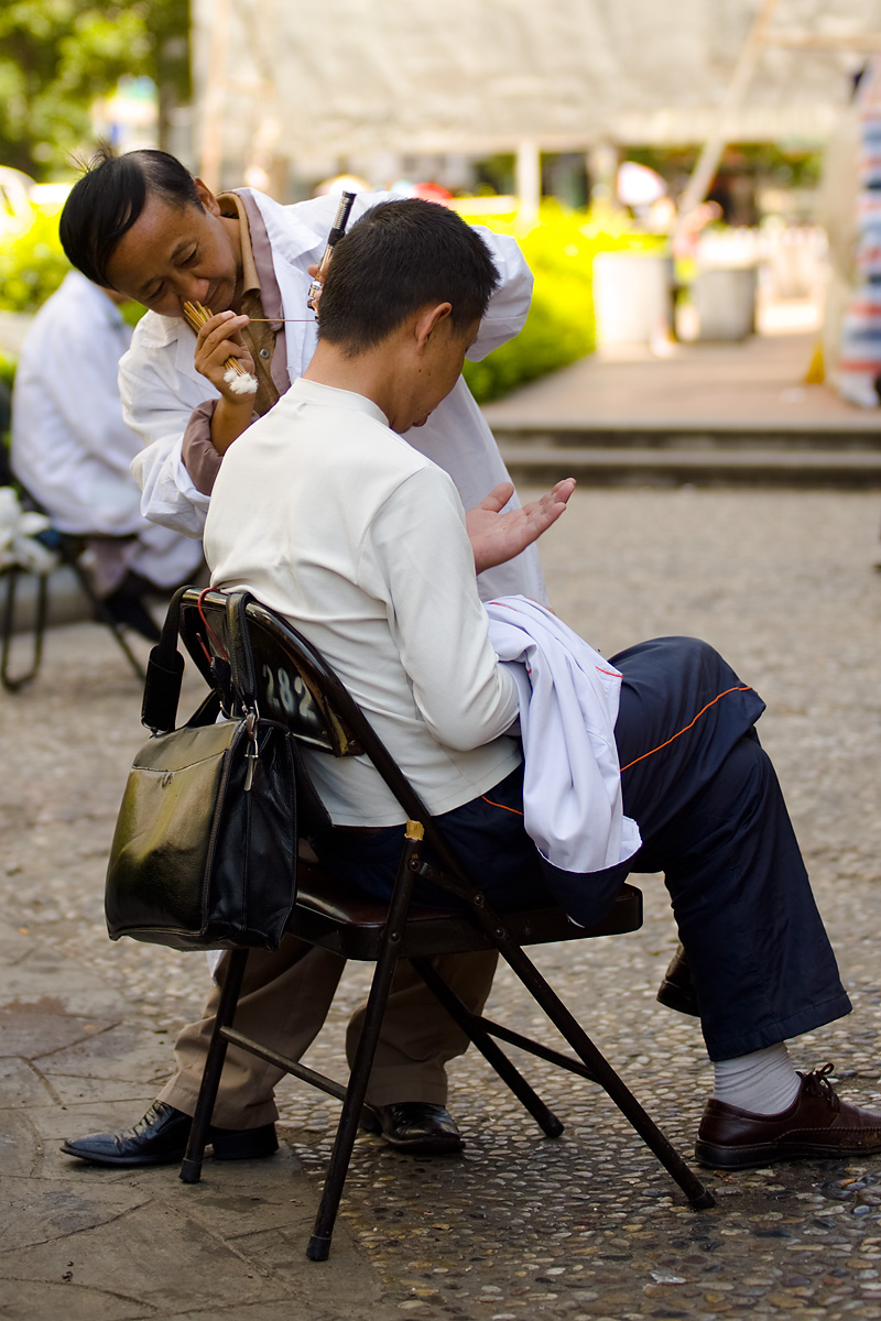 A street earwax removal technician carefully extracts the contents of a patient's ear.  - Guiyang, Guizhou, China - Daily Travel Photos