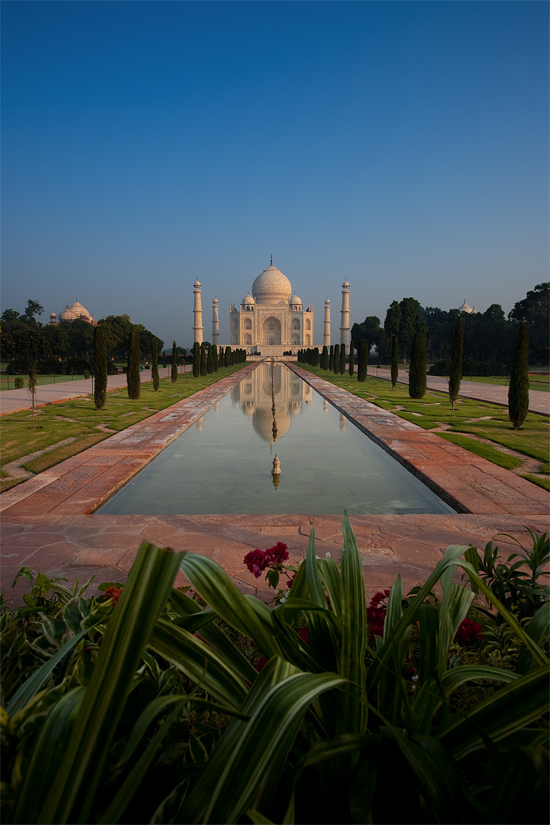 A distant view of the Taj Mahal at sunrise reflected in the first of two fountains. - Agra, Uttar Pradesh, India - Daily Travel Photos