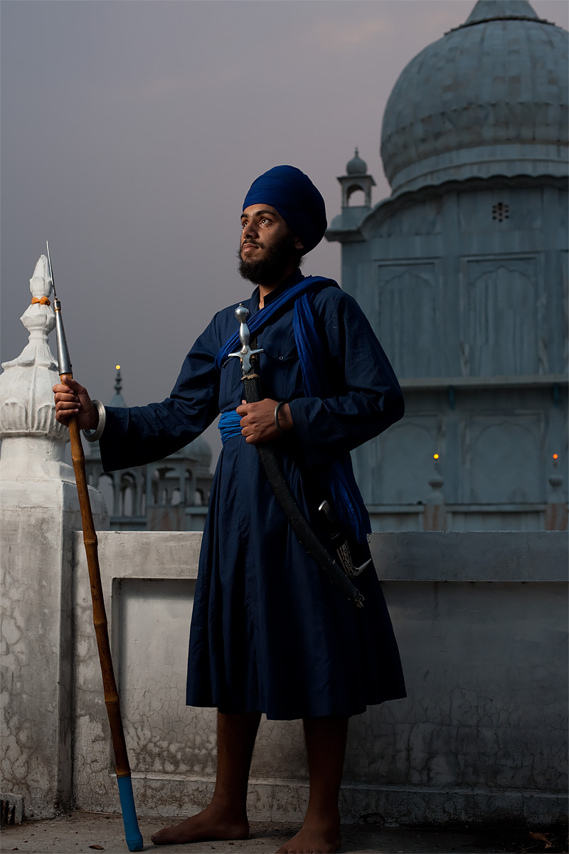 A Sikh man holds a spear, sword and dagger at the Paonta Sahib Gurudwara. - Paonta Sahib, Himachal Pradesh, India - Daily Travel Photos