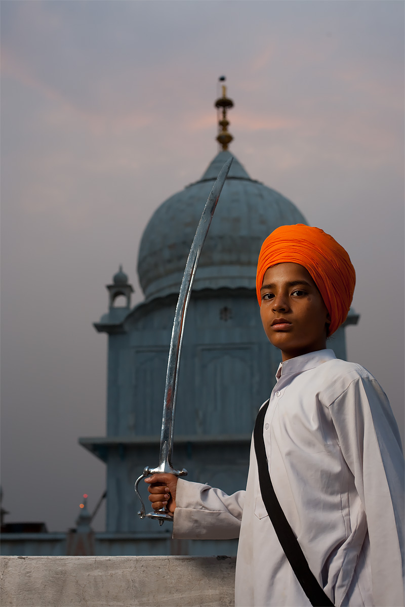 A young Sikh boy looks menacing with a sword at Paonta Sahib Gurudwara. - Paonta Sahib, Himachal Pradesh, India - Daily Travel Photos