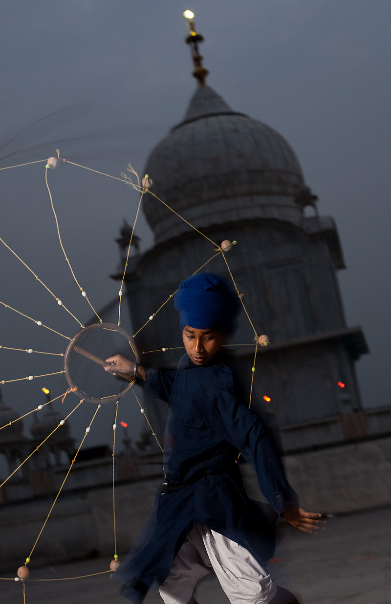 A young Sikh showman shows off his martial arts skills with a net-like weapon at the Paonta Sahib gurudwara. - Paonta Sahib, Himachal Pradesh, India - Daily Travel Photos