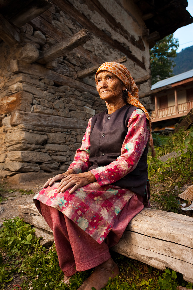 A local woman sits in front of her traditionally built house. - Sarahan, Himachal, India - Daily Travel Photos