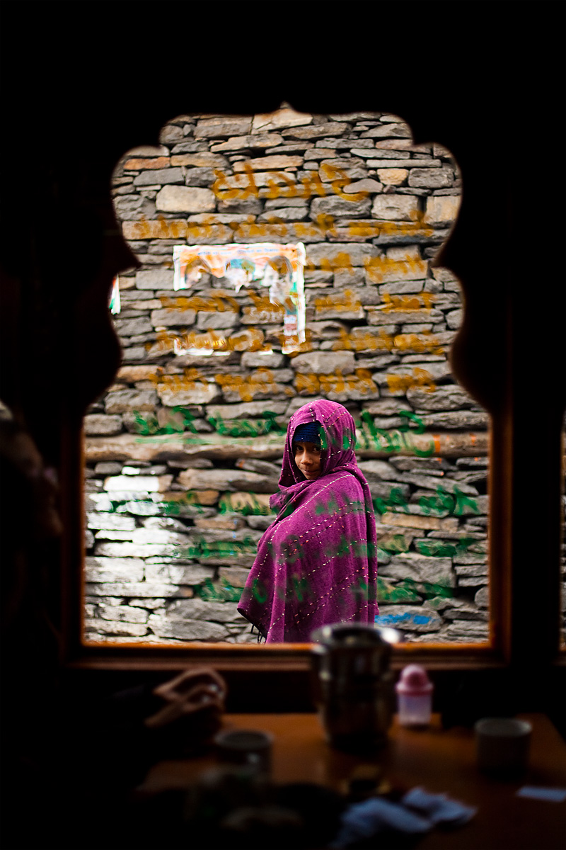 Cloaked Indian girl walks outside of a tourist cafe. - Kalpa, Himachal Pradesh, India - Daily Travel Photos