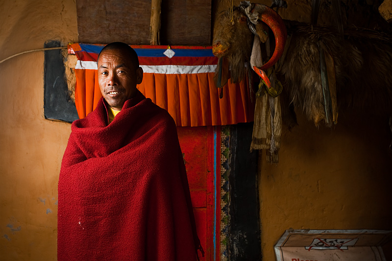 A Buddhist monk stands in a small monastery inside the temple complex of Dhankar. - Dhankar, Himachal Pradesh, India - Daily Travel Photos