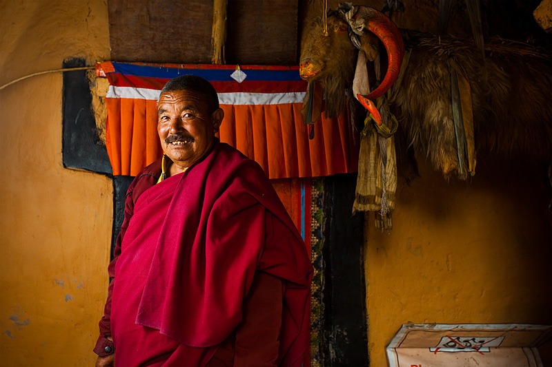 A Buddhist monk poses in front of a colorful wall. - Dhankar, Himachal Pradesh, India - Daily Travel Photos