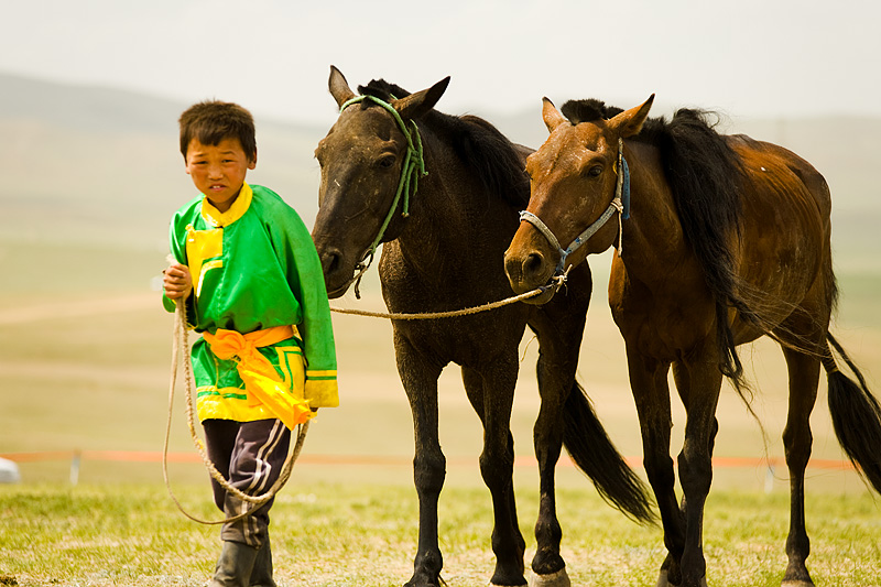 A young Mongolian boy walks horses around the prarie. - Ulaan Baatar, Mongolia - Daily Travel Photos