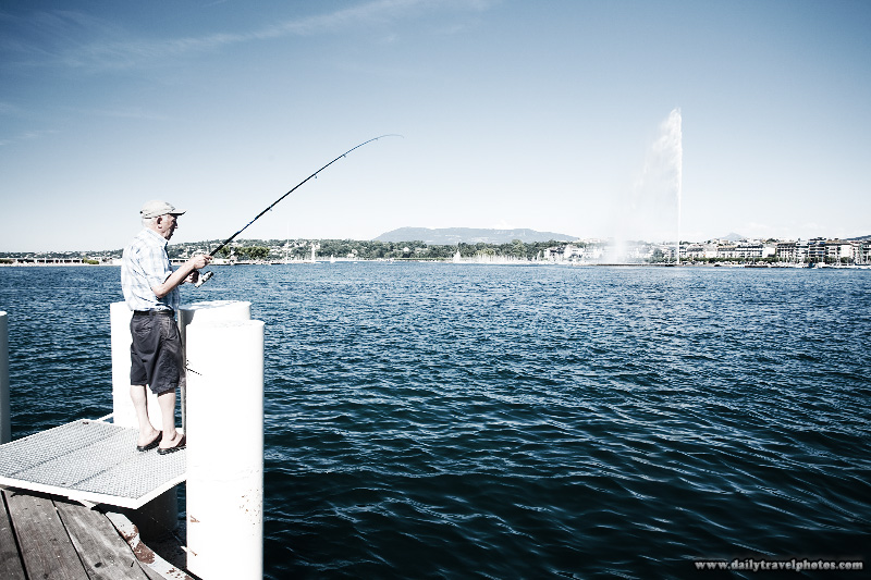 A Swiss man fishes from a boat dock in Lake Geneva - Geneva, Switzerland - Daily Travel Photos