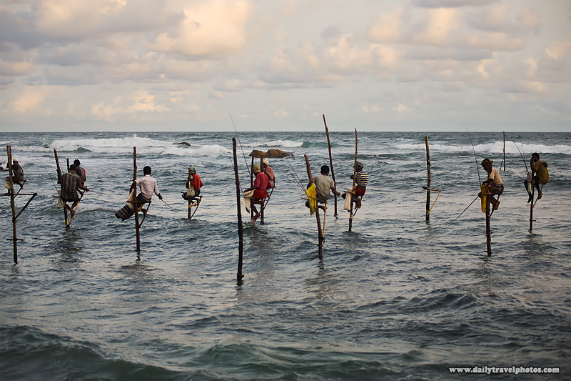 A group of Sri Lankan stilt fishermen fish in a rough ocean. - Unawatuna, Sri Lanka - Daily Travel Photos