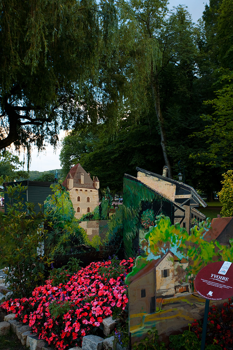 A miniature cutout of a castle displayed at a park by the lake - Annecy, France - Daily Travel Photos