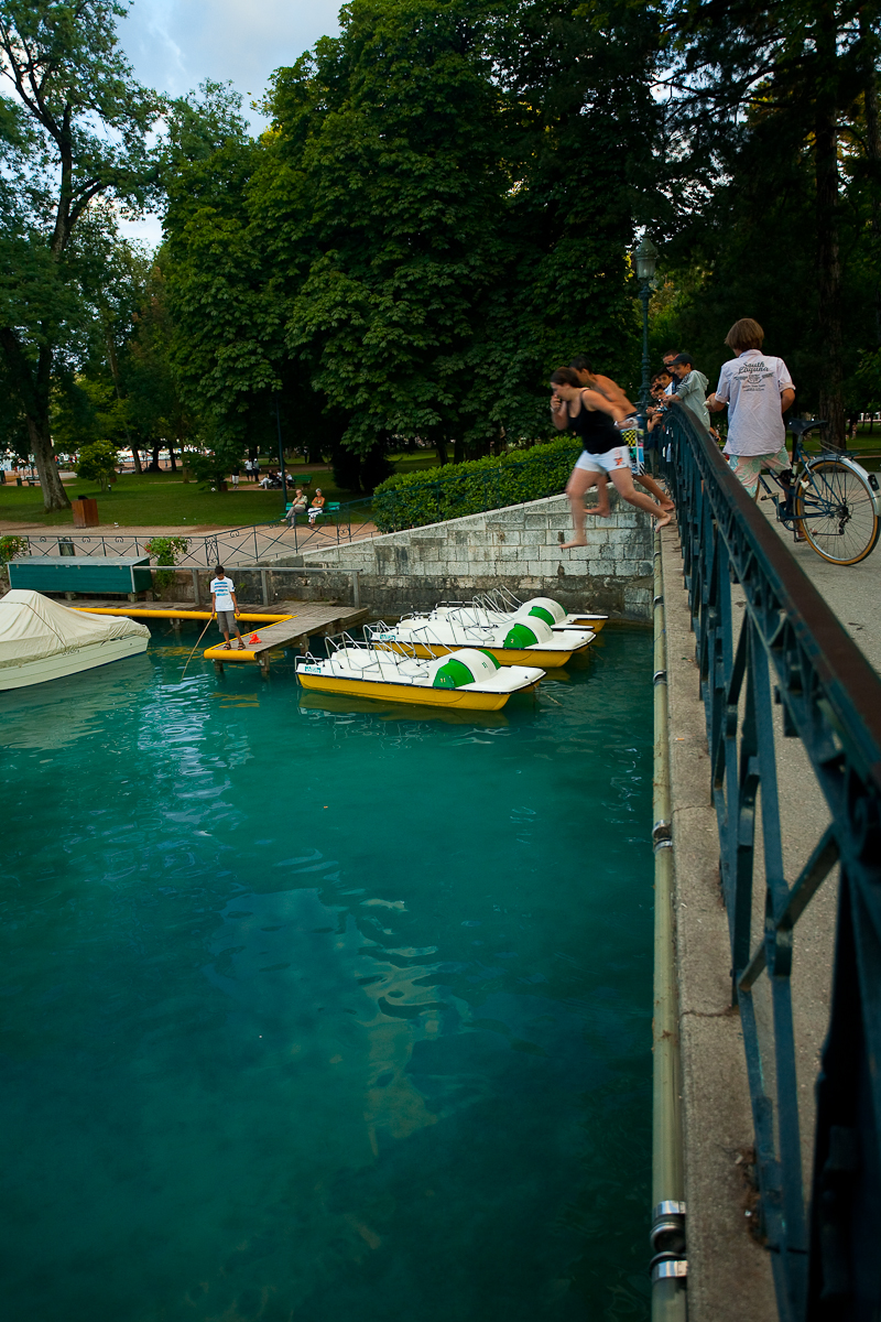 French children jump from a bridge into beautiful lake Annecy - Annecy, France - Daily Travel Photos