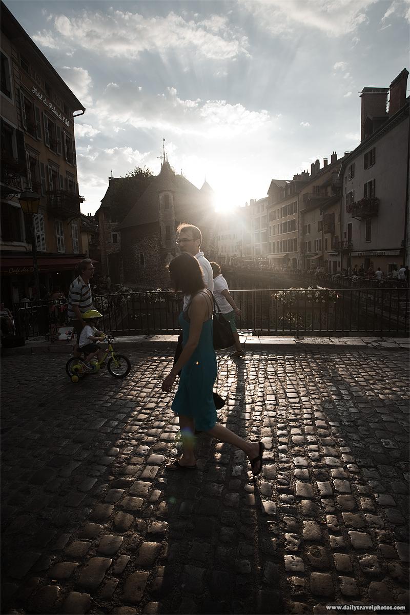 French tourists around the cobblestone Palais de L'isle bridge - Annecy, Haute-Savoie, France - Daily Travel Photos
