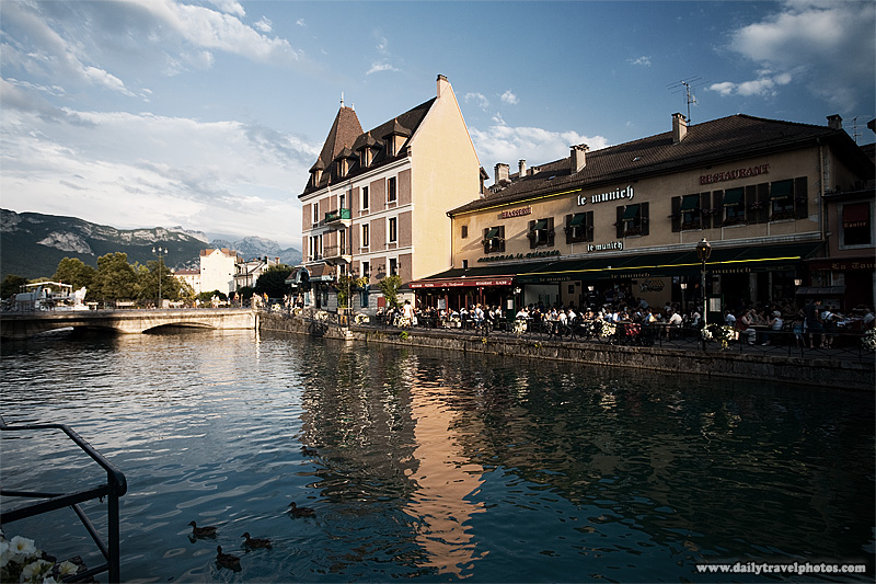 Restaurants line the canal as the Alps tower in the background - Annecy, Haute-Savoie, France - Daily Travel Photos