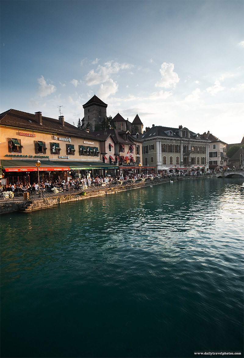 Tourists dine on the waterfront as the Annecy castle towers behind - Annecy, Haute-Savoie, France - Daily Travel Photos