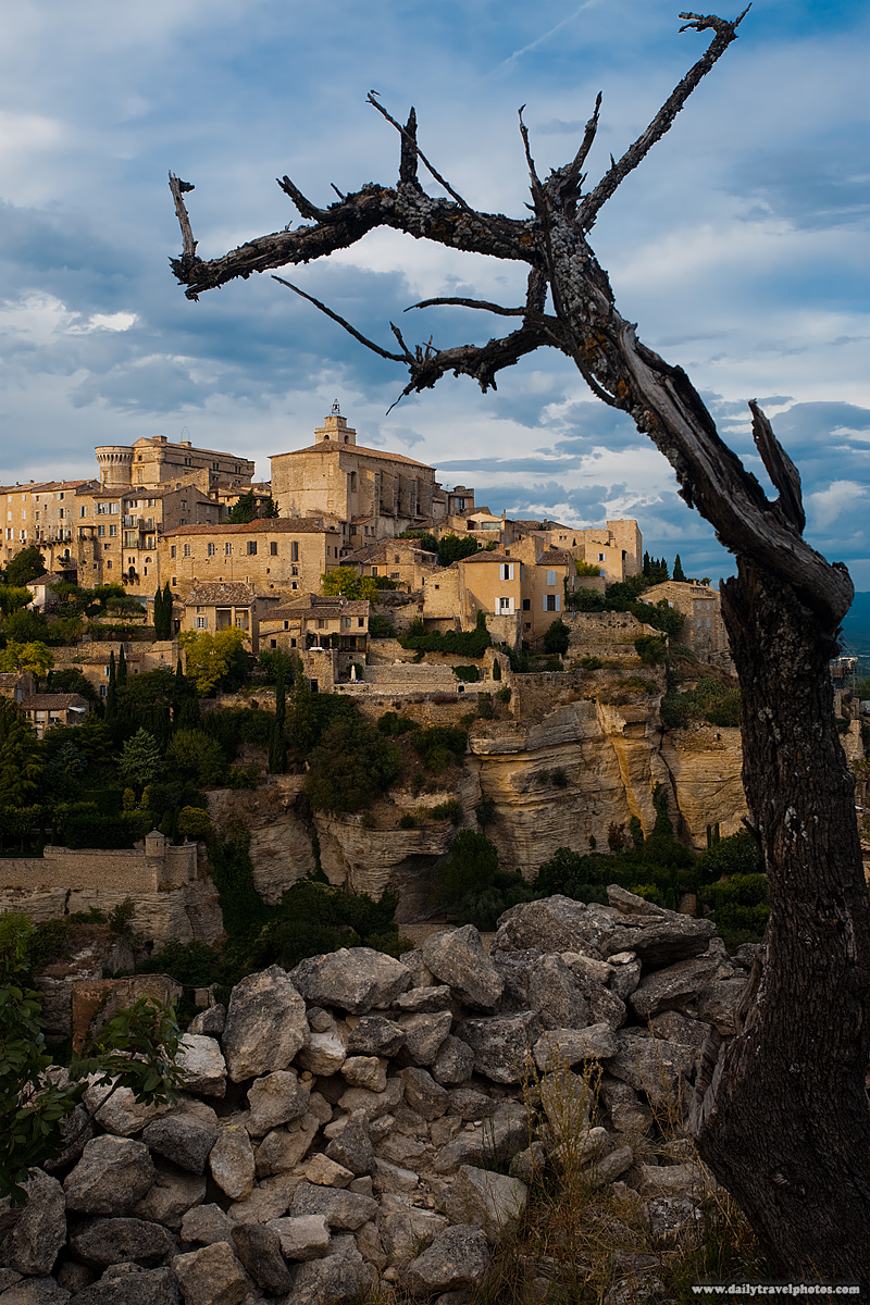 Picturesque and most beautiful mountaintop village in Provence framed by tree and rock fence - Gordes, Provence, France - Daily Travel Photos