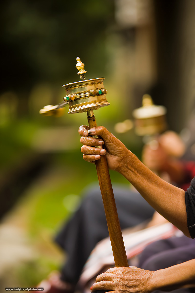 Tibetan women spin a mani, a prayer wheel while chanting mantras  - Rangwu, Tibet - Daily Travel Photos