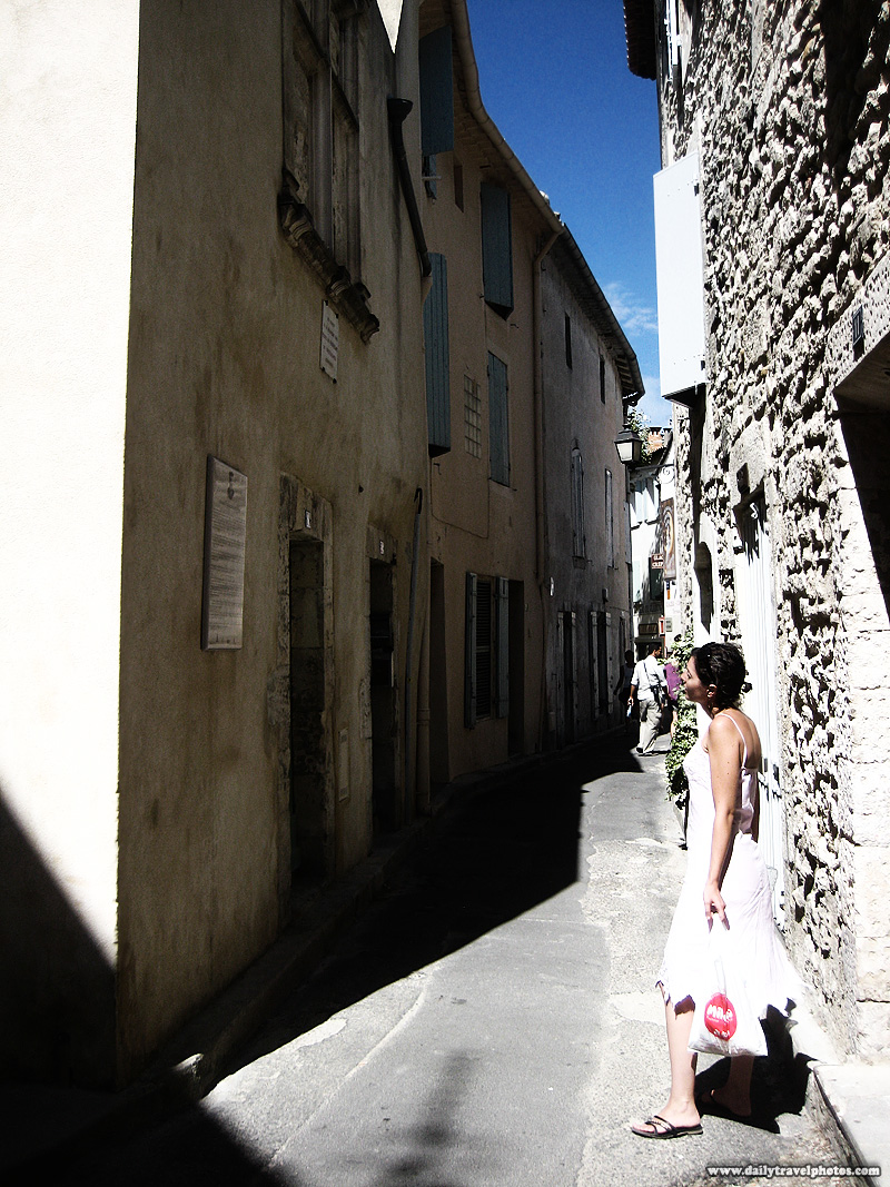 A young woman reads the plaque outside of Nostradamus' house - Saint Remy de Provence, Provence, France - Daily Travel Photos