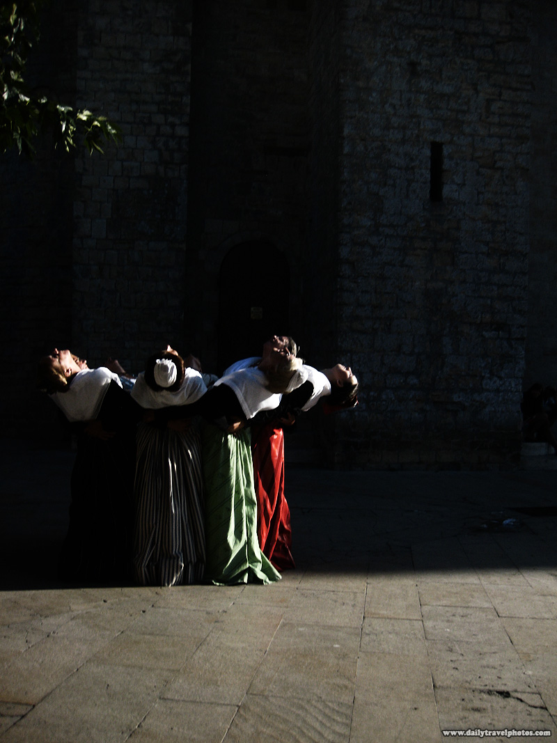 Traditionally dressed women in period costume bend backwards in a choreographed dance - Saintes Maries de La Mer, Provence, France - Daily Travel Photos