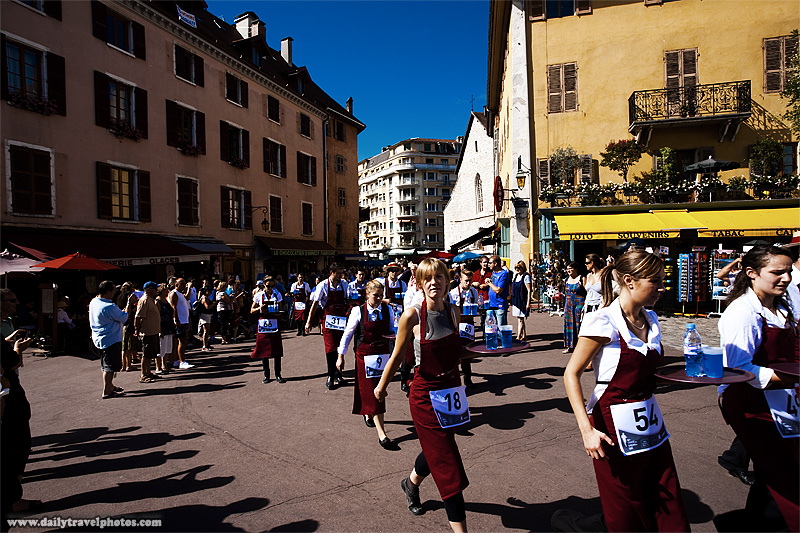 Monthly fun waiter's run through old city while balancing items on a tray - Annecy, Haute-Savoie, France - Daily Travel Photos