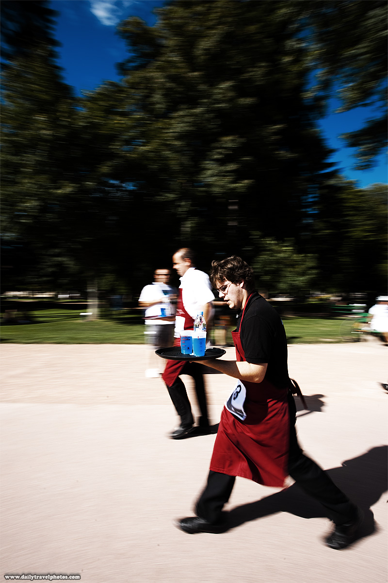 Concentrating male contestant in monthly Waiter's Run - Annecy, Haute-Savoie, France - Daily Travel Photos