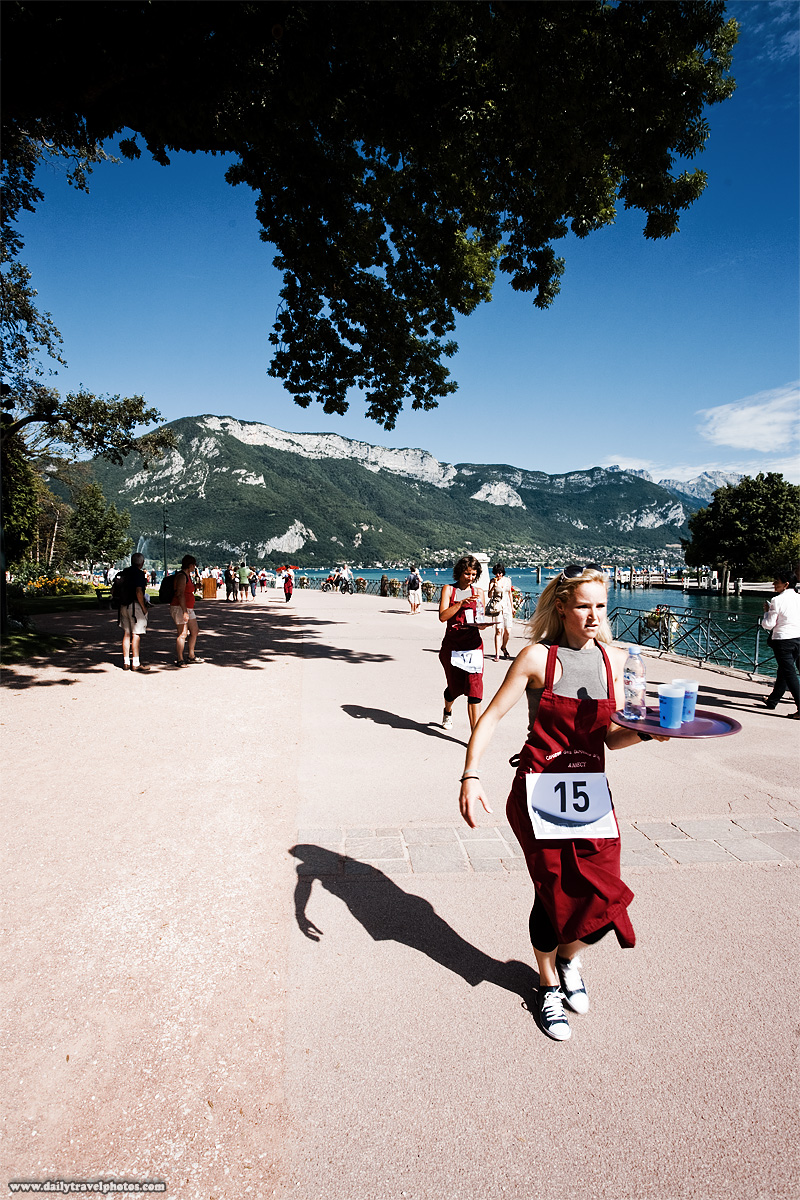 Waiter's Run by Lake Annecy Alps background female waitresses carrying drinks. - Annecy, Haute-Savoie, France - Daily Travel Photos