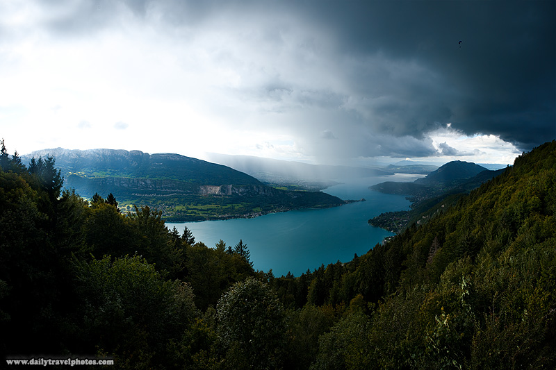 A paraglider braves storm clouds for a fly in the sky over Annecy Lake - Col de La Forclaz, Haute-Savoie, France - Daily Travel Photos