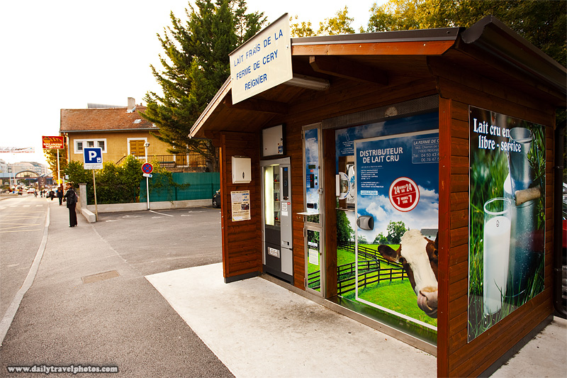 Curbside milk vending machine housed in a rustic shed - Gaillard, Haute-Savoie, France - Daily Travel Photos
