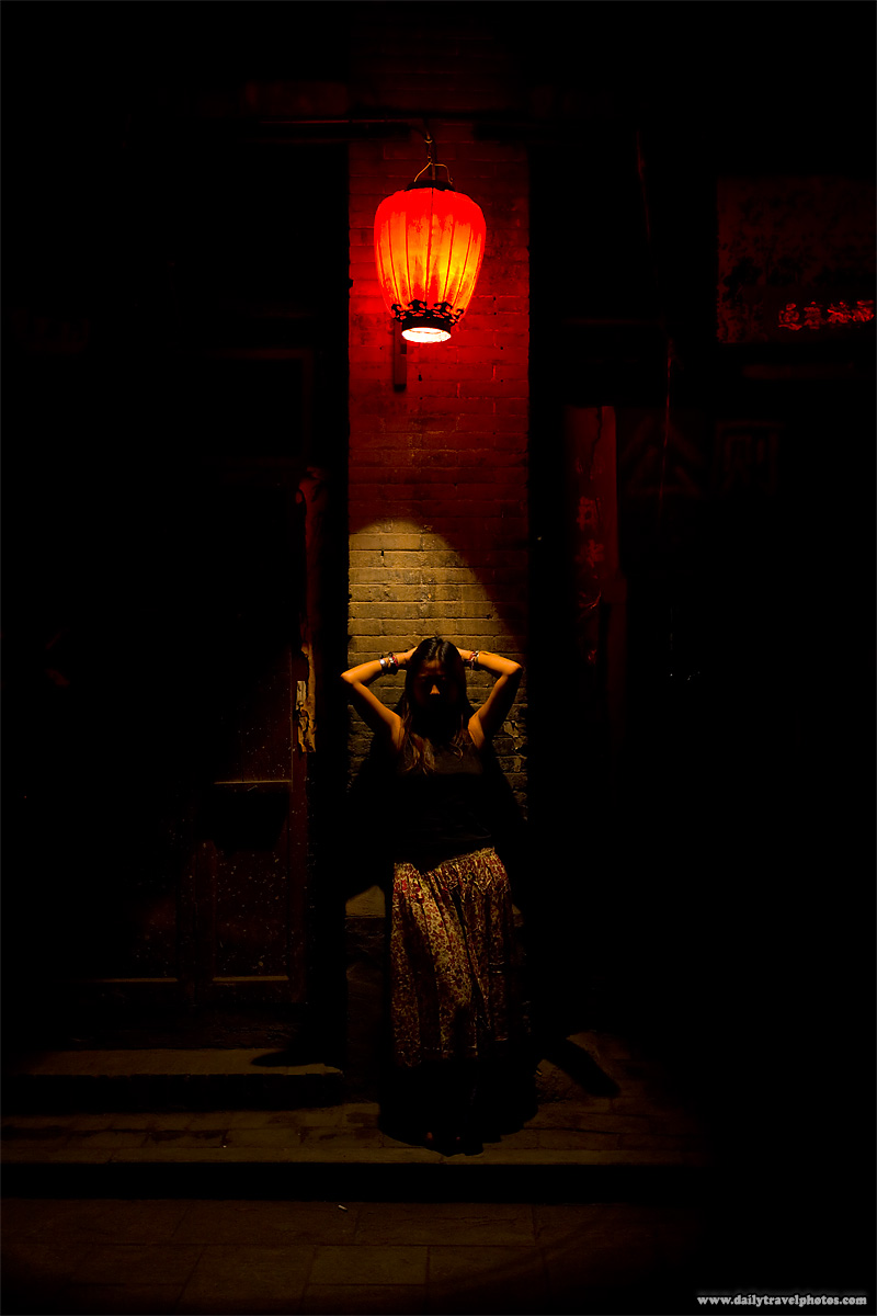 A beautiful young woman poses under a red Chinese lantern on a traditional village street - Pingyao, Shanxi, China - Daily Travel Photos
