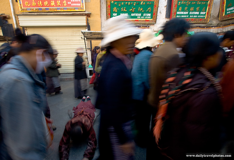 A Tibetan pilgrim prostrates sideways around the Barkhor - Lhasa, Tibet - Daily Travel Photos