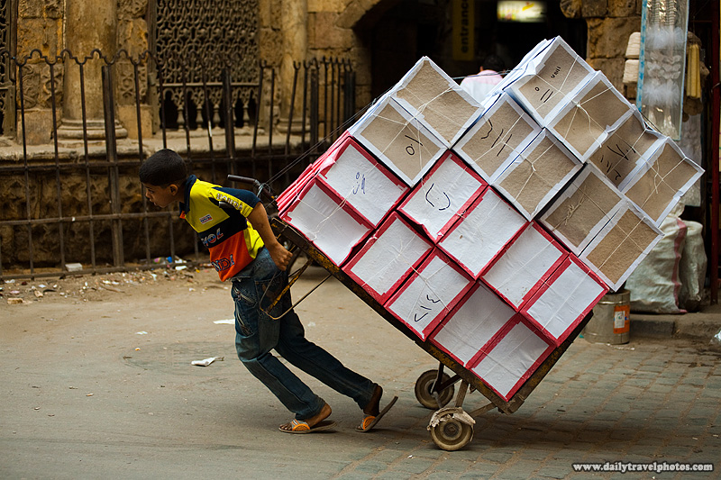 A young Egyptian boy struggles to pull a dolly full of merchandise - Cairo, Egypt - Daily Travel Photos